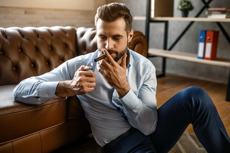 Young handsome businessman smoke cigar in his own office. He sit on floor and lean to sofa. Guy hold cigarette lighter. Sexy and concentrated Stock Photo