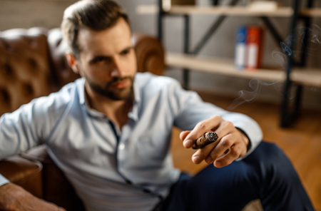 Young handsome businessman sit on floor and hol cigar in his own office. He look straight with confidence. Cool and sexy