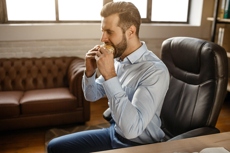 Young handsome businessman eat burger in his own office. He sit at table and bite meal. Unhealthy delicious. Break. Daylight Stock Photo