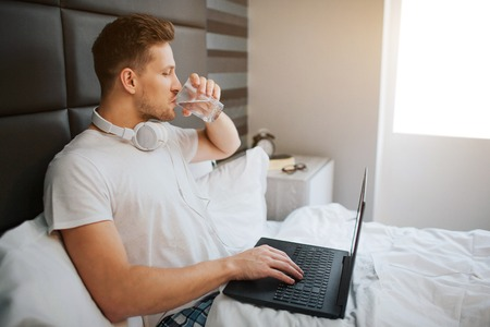 Young handsome man sit in bed this morning. He drink water. Male model hold laptop. Headphones around neck Stock Photo