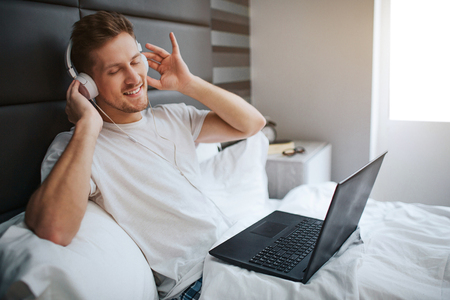 Young man sit in bed early morning. He enjoying listen to music through headphones. Positive guy has laptop on bed. Daylight