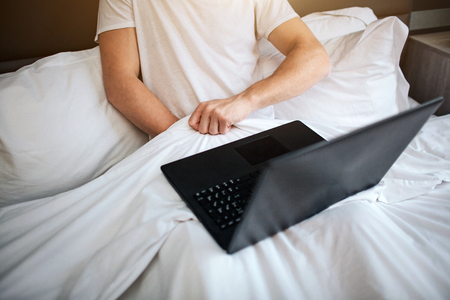 Young man sit in bed early morning. He hold hand under white blanket and masturbating. Laptop on his legs. Watching video
