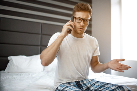Serious young man sit on bed at home in room. He talk on phone emotionally. Guy wave with hand. Daylight Stock Photo