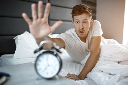 Young amazed man lyin on bed in morning. He overslept. Guy reach clock Stock Photo