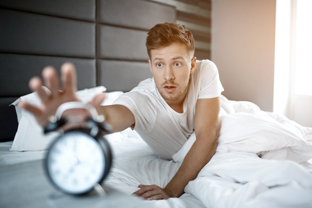 Disturbed young man lying on bed in morning. He overslept. Guy reach clock with hand