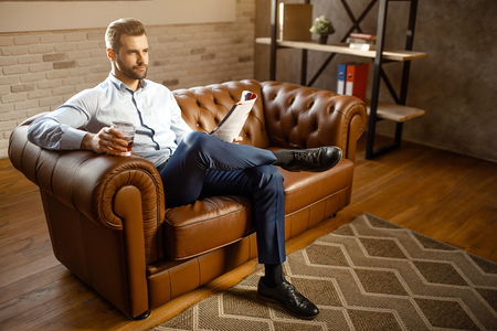 Young handsome buisnessman sitting on sofa and drink whiskey in his own office. He look straight with confidence. Guy hold journal. Attractive small smile