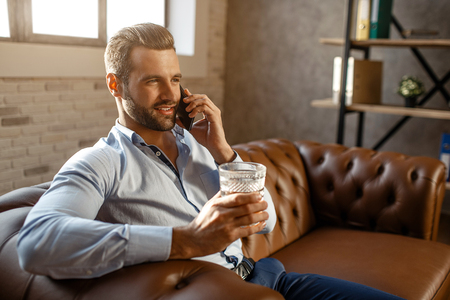 Young handsome businessman sit on sofa and talk in his own office. He hold glass of whiskey in hand and smile. Confident and sexy. Happy and cheerful Stock Photo