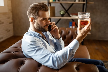 Young handsome businessman sit on sofa and look at glass of whiskey in hand in his own office. Guy talk on phone. Serious and concentrated. Sexy young man Stock Photo