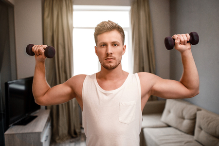 Young well-built man go in for sports in apartment. He does shoulder press using dumbbells. Guy look on camera serious. Strong and muscled guy Stock Photo