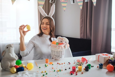 Happy positive young woman prepare fo Easter alone. She sit at table in room and hold yellor egg. Basket in front. She smile. Decoration and sweets on table