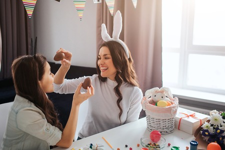 Cheerful mother and daughter prepare for Easter. They hold chocolate eggs and smile. Decoration on table. Model wear white rabbit ears. 写真素材