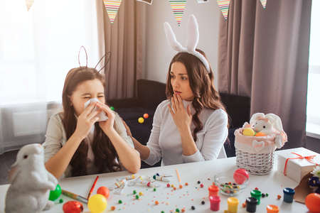 Mother and daughter prepare for Easter together. Sick girl sneezing. Young woman worry. Easter decoration with painting and sweets on table.