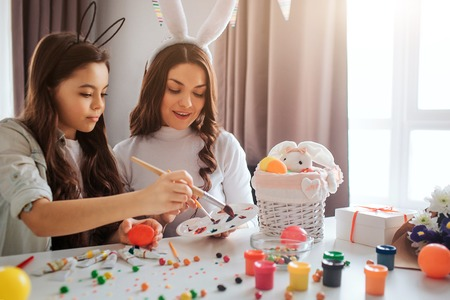 Mother and daughter prepare for Easter together. They hold paint brushes and get some color for eggs. Decoration and sweets all over table. Concentrated people.
