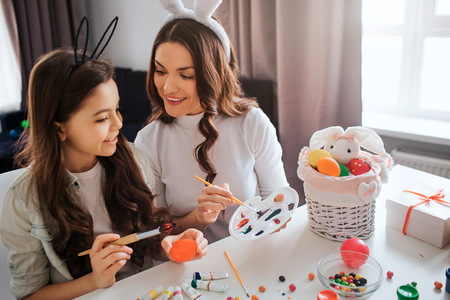 Lovely mother and daughter prepare for Easter. They paint eggs in room. Girl hold brush. Mother point on pallete. Working together. Cheerful and positive.