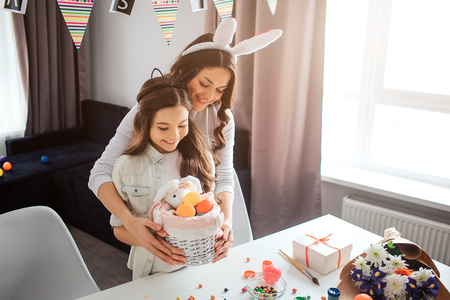 Cheerful mother and daughter stand at table and prepare for Easter in room. They hold basket with eggs and sweets together. People wear buny ears on head. Daylight