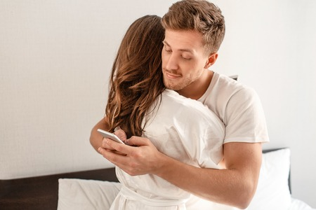 Young couple in the bedroom after waking up. Smiling unfaithful man is cheating and texting lover on the phone while hugging his girlfriend Stock Photo