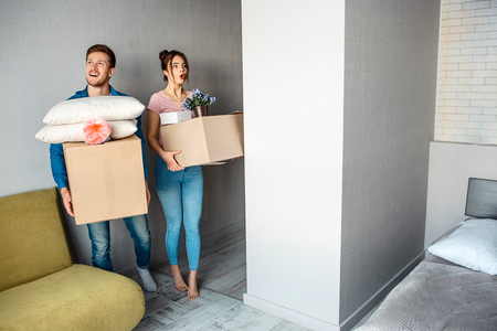 Young family couple bought or rented their first small apartment. Beautiful people enter room and carry boxes with stuff. Excited and amazed. Archivio Fotografico