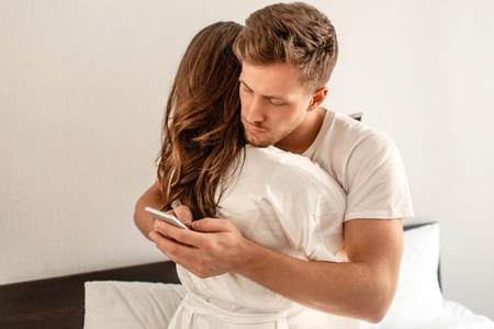 Young couple in the bedroom after waking up. An attractive man is checking incoming messages in the morning Stock fotó
