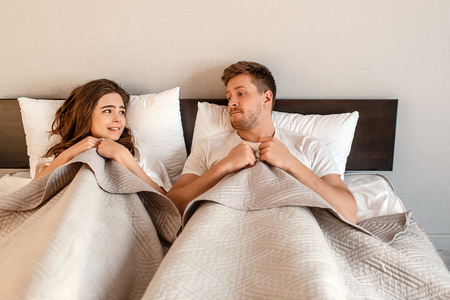 Young couple in the bed. Fear of sex, shy woman and man hidding under blanket before