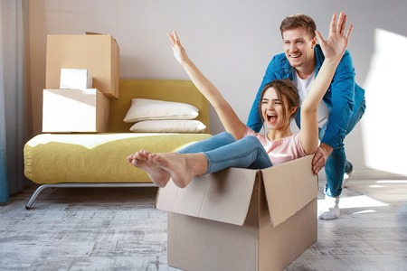 Young family couple bought or rented their first small apartment. Cheerful happy people having fun. She sit in box and scream. Guy move her. Moving and unpacking Stock Photo