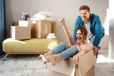 Young family couple bought or rented their first small apartment. Cheerful woman scream sitting in box. Guy move her. They play game during moving in Stock Photo