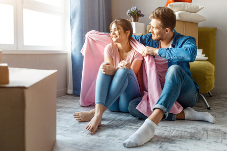 Young family couple bought or rented their first small apartment. Happy people sit together on floor and look at window. He hugs her. Moving in. Unpacking Stock Photo