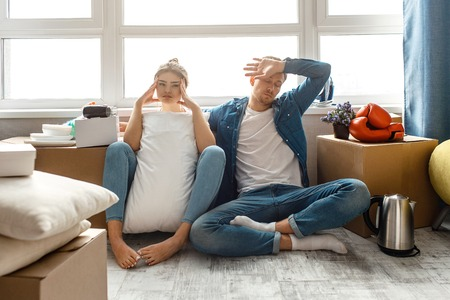 Young family couple bought or rented their first small apartment. Tired exhausted people sit on floor after moving in Stock Photo
