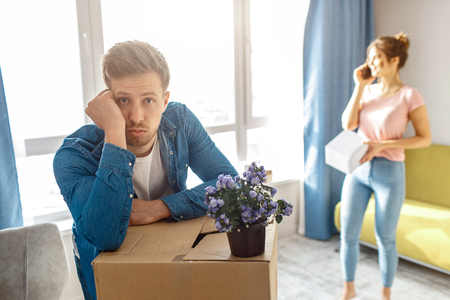 Young family couple bought or rented their first small apartment. Bored guy lean to cardboard. Young woman talk on phone. Flower in potty stand on box. Unpacking and moving in Stock Photo