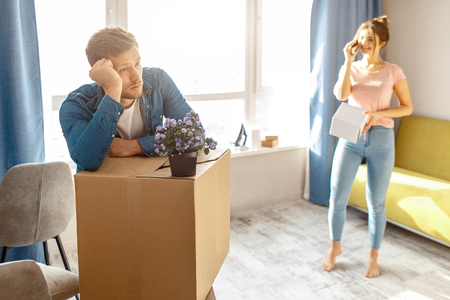 Young family couple bought or rented their first small apartment. Bored man lean on box. Young woman talk on phone. People unpacking after moving into apartment