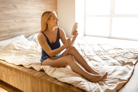 Young beautiful blonde woman sitting in bed in morning. She hold glass bottle in hand and look at it. She smile. Daylight