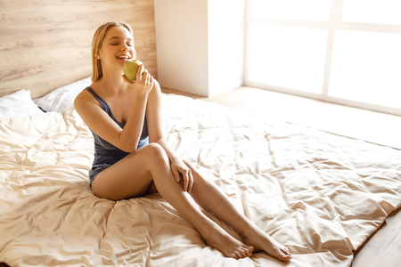 Young beautiful blonde woman sitting in bed in morning. She hold big green tasty apple in hand and look at it. Model posing. Daylight