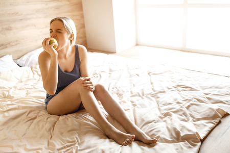 Young beautiful blonde woman sitting in bed in morning. Model bite peace of apple and look to side. She concentrated on eating apple. Daylight Stock Photo