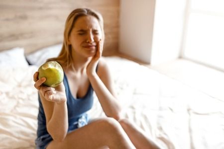 Young beautiful blonde woman sitting in bed in morning. Model suffer from tooth ache. She hold hand on cheek. Bitten apple in another hand. She show it to camera Stock Photo