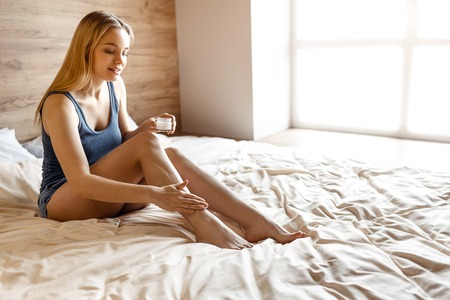 Young beautiful blonde woman sitting in bed in morning. She put some body cream onto leg. Take care of skin. Concentrated. Slim and well-built. Daylight Stock Photo