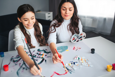 Beautiful brunette  mother and daughter paint together in room. Happy girl hold brushes with mom.