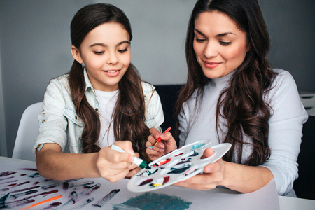 Beautiful brunette caucasian  mother and daughter paint together in room.