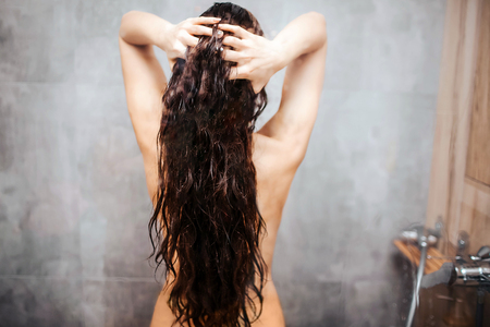 Young attractive woman in shower. Dark-haired model with well-built slim body stand and hold hair between hands.