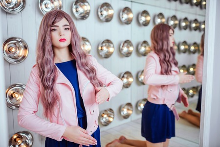 Fashion freak. Glamour synthetic girl, fake doll with empty look and long lilac hair is sitting in the studio. Stylish beautiful woman in blue dress near light bulbs. Fashion and beauty concept