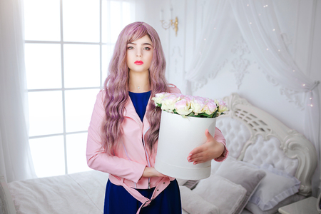 Fashion freak. Glamour synthetic girl, fake doll with empty look and long lilac hair is holding box with flowers while standing in white bedroom. Stylish beautiful woman in blue dress. Beauty concept