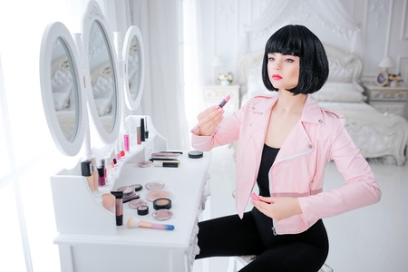 Fashion freak. Glamour synthetic girl, fake doll with empty look and short black hair is holding lipstick while sitting near mirror. Stylish woman in pink jacket in white bedroom. Fashion and beauty concept Stock Photo