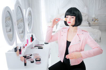 Fashion freak. Glamour synthetic girl, fake doll with empty look and short black hair is holding brush while sitting near mirror. Stylish woman in pink jacket in white bedroom. Fashion and beauty concept