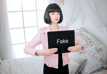 Fashion freak. Glamour synthetic girl, fake doll with empty look and short black hair is holding paper with word Fake while standing near the bed. Stylish woman in pink jacket in the white bedroom. Sexism concept