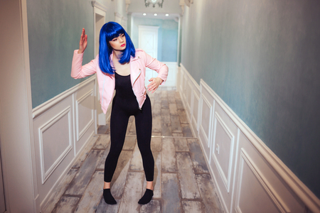 Fashion freak. Glamour synthetic girl, fake doll with empty look and blue hair is moving in long corridor. Stylish woman in pink jacket in the house. Fashion and beauty concept