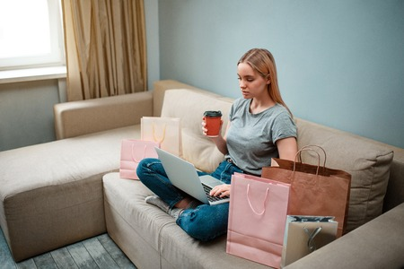 Online shopping at home. Young serious shopper with coffee is using laptop while sitting on sofa with shopping bags Stock Photo