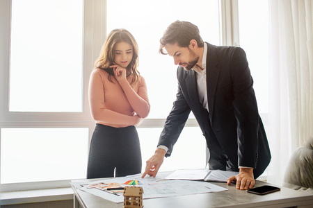 Couple buy or rent apartment together. They stand upon table and hold there plan. Young man look at it. He lean to table. Young woman look down too and pose. Daylight.