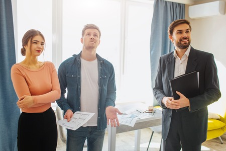 Couple buy or rent apartment together. They stand with realtor. Young man look up. Woman has doubts. Cheerful realtor look rorward. Фото со стока