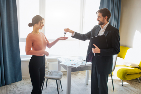 Young woman buy rent apartment. She get keys from realtor. Happy and joyful. Business deal in office room. Bright daylight.