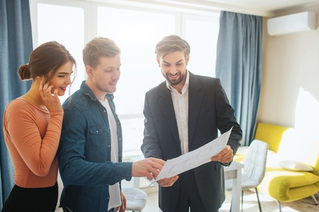 Couple buy or rent apartment together. Realtor and man hold plan together and look at it. Woman stand behind guy. Business deal. Happy and positive.