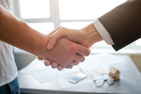 Close up cut view shaking hands of two men. Table with apartment plan and window on back. Bright background.