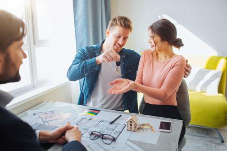 Paare kaufen oder mieten gemeinsam eine Wohnung. Glückliche junge Frau bekommt Schlüssel vom Mann. Makler sitzen vor ihnen. Wohnungsplan und Telefon auf dem Tisch. Standard-Bild